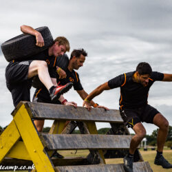 Folks help each over in a mud race with obstacle course. In a motion