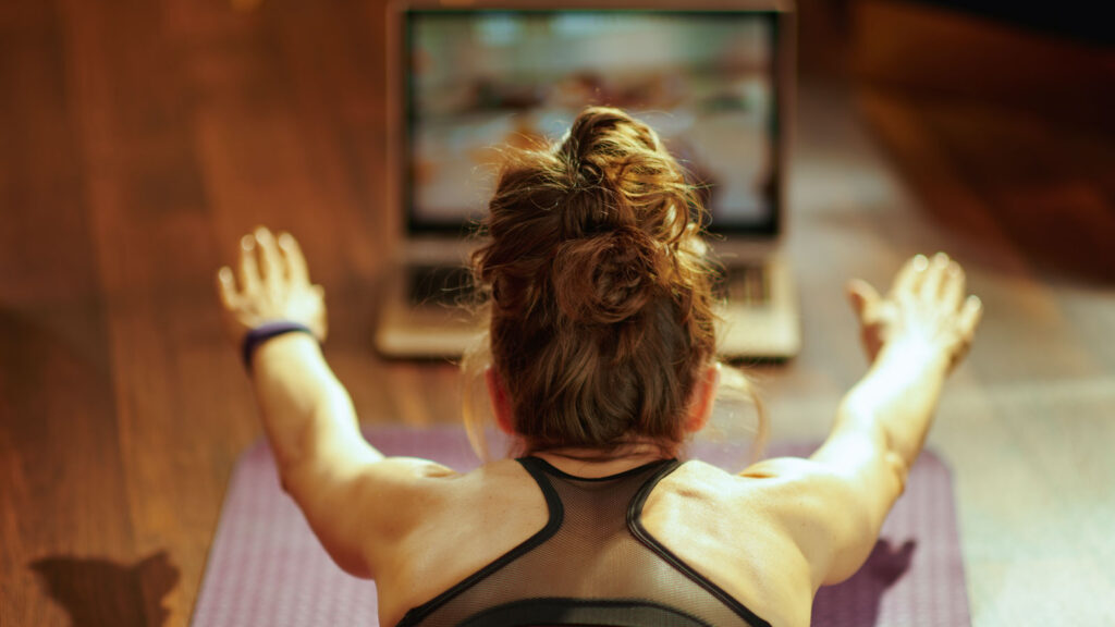 woman watching fit tutorial on internet while doing exercises
