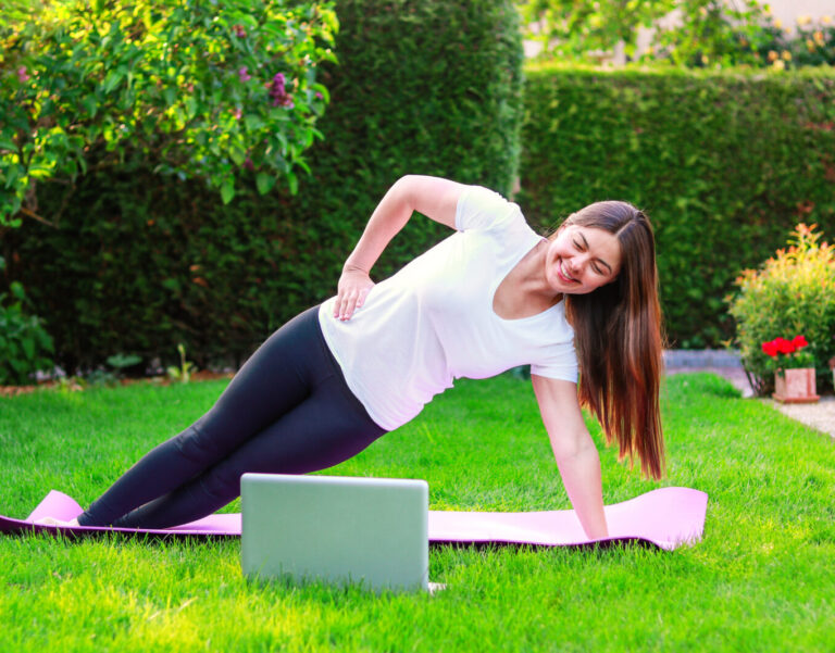 Beautiful young woman doing sport in garden outdoors following guide of online tutorial or trainer on laptop. Healthy lifestyle. Exercising at home. Doing fitness online